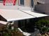 Toldo modelo extensible tipo cofre lona lisa blanca instalado en un patio