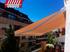 Toldo modelo extensible tipo cofre lona lisa naranja instalado en un ático